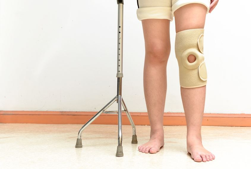 Woman walking on cane , wearing knee support in rehab center